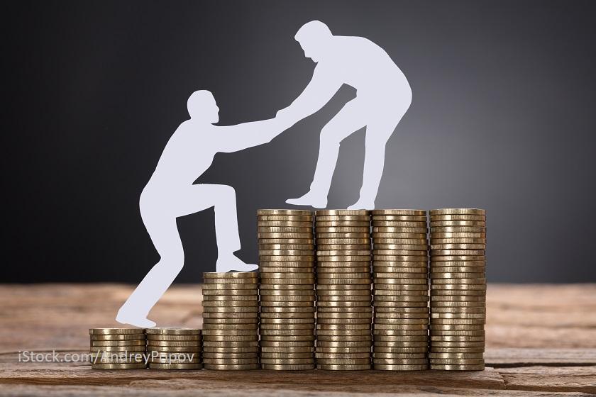 Zwei Personen erklimmen einen Geldberg. Die eine Person hilft der anderen.