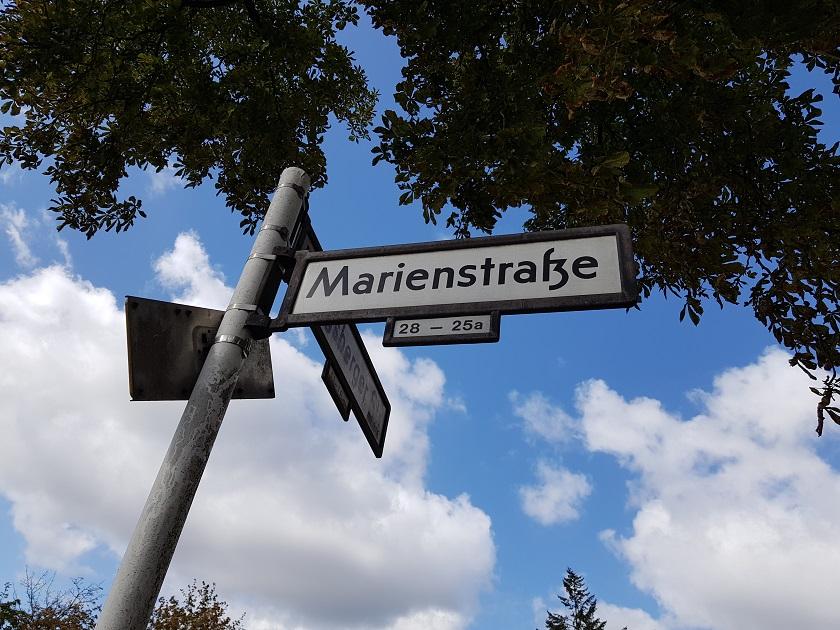 Ein Straßenschild zeigt die Marienstraße an. Im Hintergrund befinden sich Baume, Himmel und Wolken.