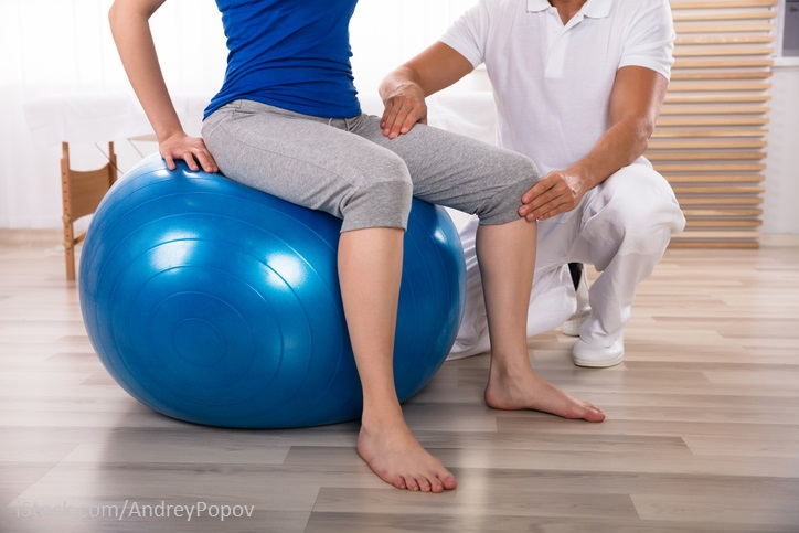 Patientin sitzt auf einem Pezziball-Therapeut zeigt Übungen