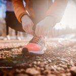 Sportlerin bindet sich den Laufschuh zu.