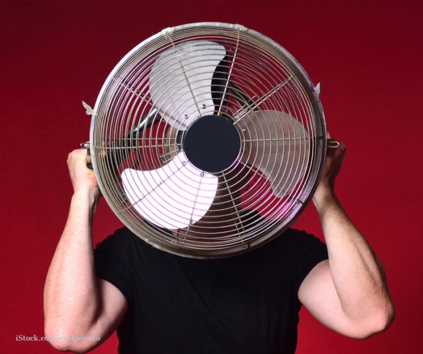 Mann haelt sich einen Ventilator vor das Gesicht
