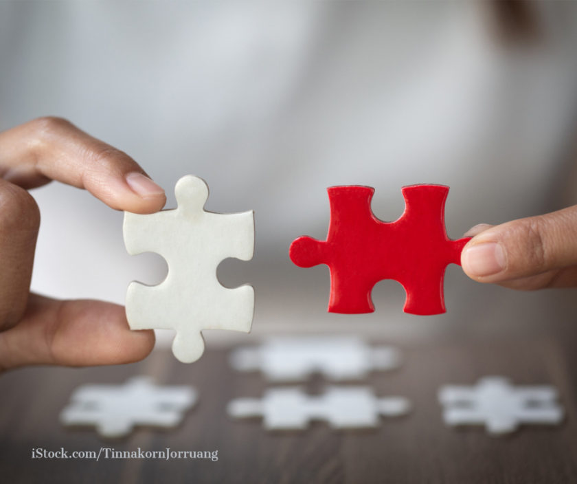 ein weißes und ein rotes Puzzleteil greifen ineinander