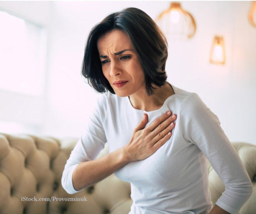 Eine Frau fasst sich schmererfuelltem Gesicht an die Brust