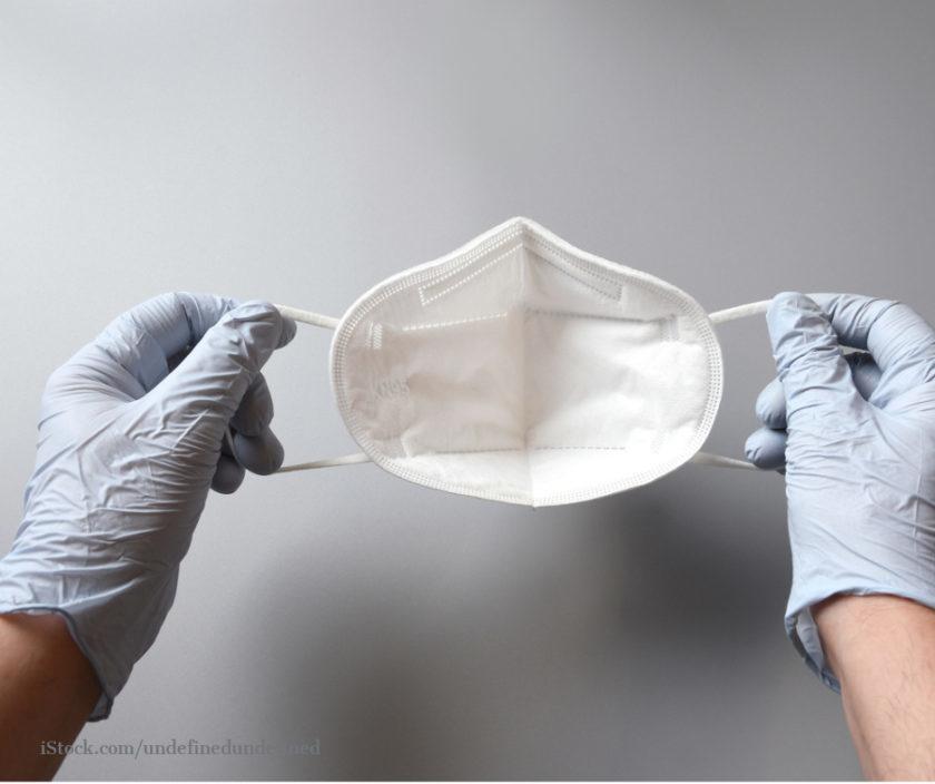 Haende mit Handschuhen bedeckt halten eine FFP2 Maske
