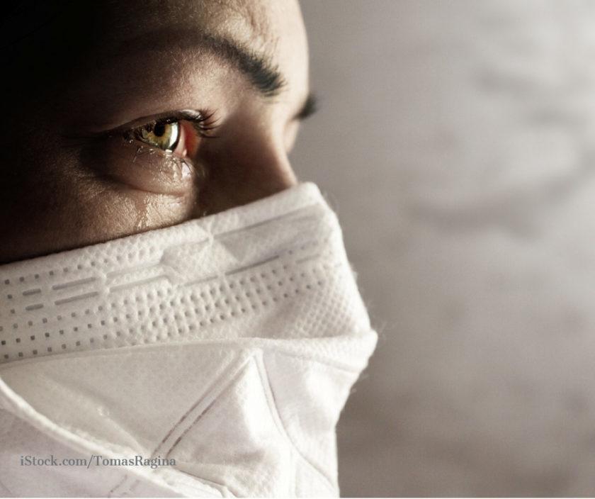 Frau mit FFP2 Maske mit Traenen in den Augen