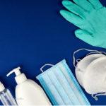 Desinfektionsmittel, Masken und Handschuhe vor blauem Hintergrund