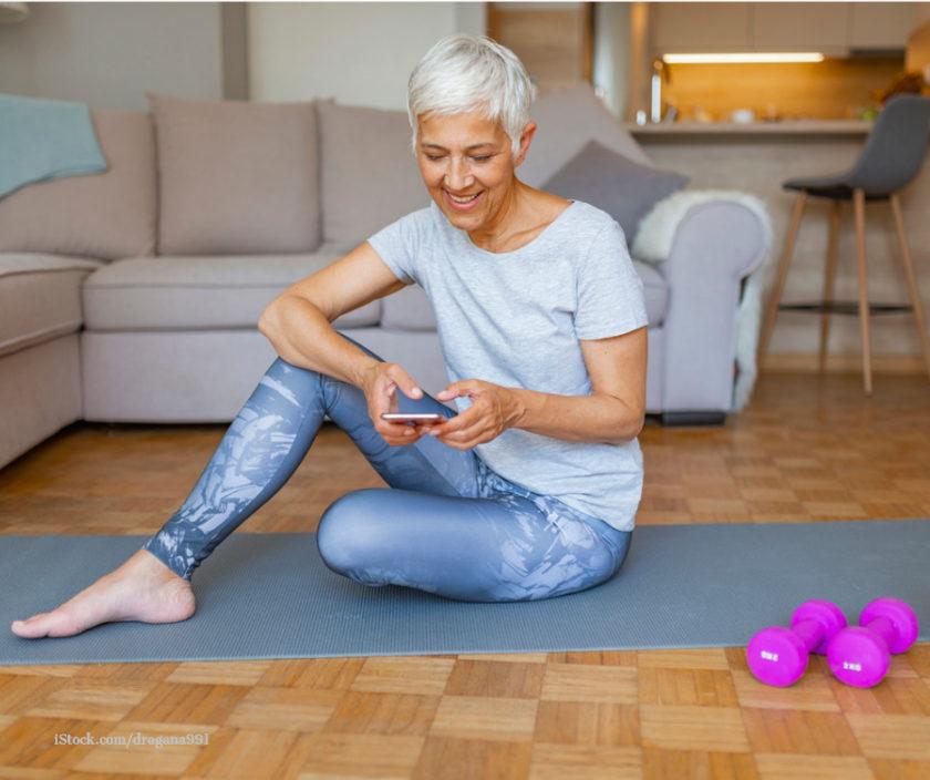 Eine Frau sitzt auf der Gymnastikmatte und haelt ein Smartphone in der Hand