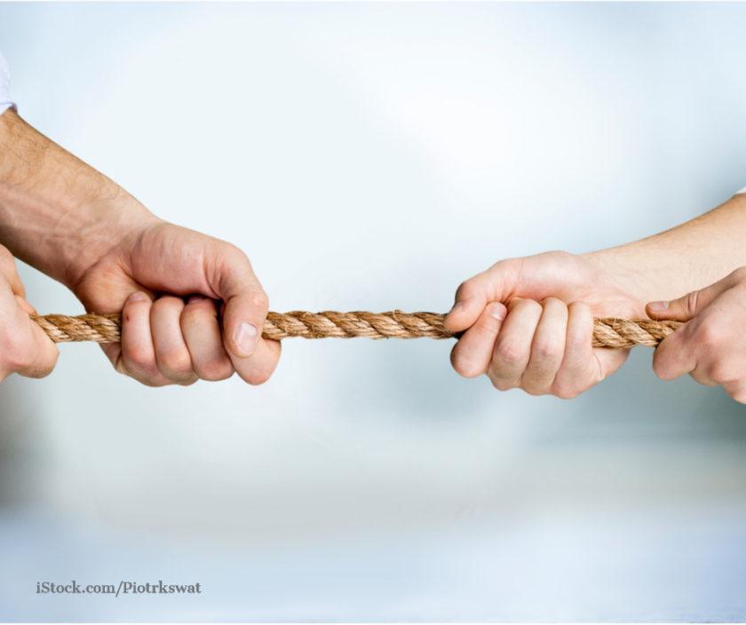 Zwei Haende zerren an einem Seil