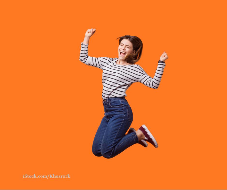 Junge Frau springt vor Freude in die Luft