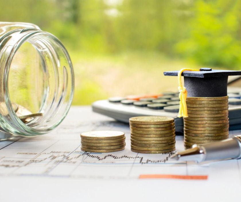 Kleingeld, Taschenrechner und Graduiertenhut
