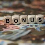 Wuerfel auf Kleingeld mit der Aufschrift Bonus