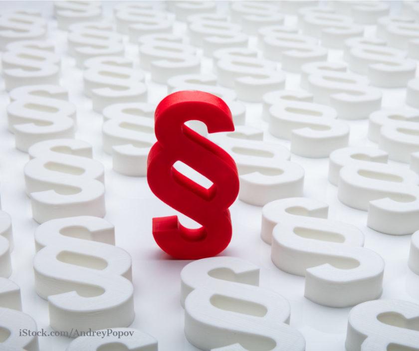 ein rotes Paragraphensymbol steht zwischen weißen Paragraphensymbolen