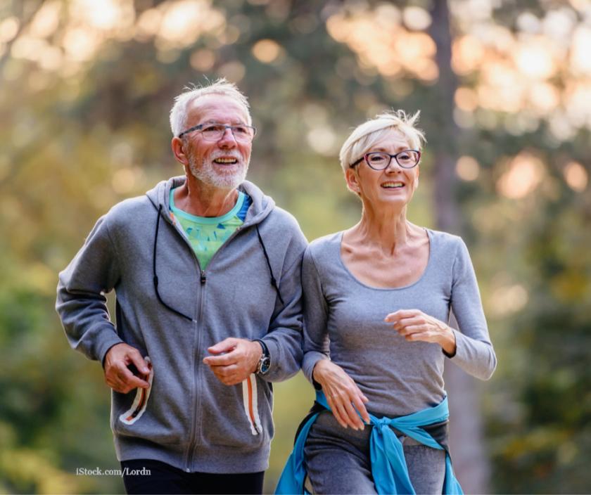 Zwei Senioren joggen gut gelaunt durch einen Park.