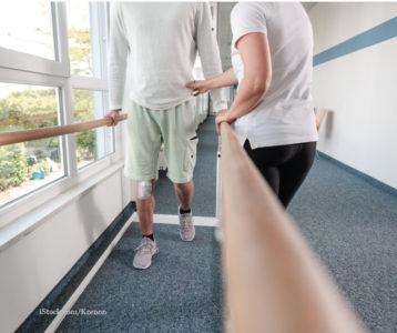 Physiotherapeutin unterweist Mann im Gehbarren in Gangschule.
