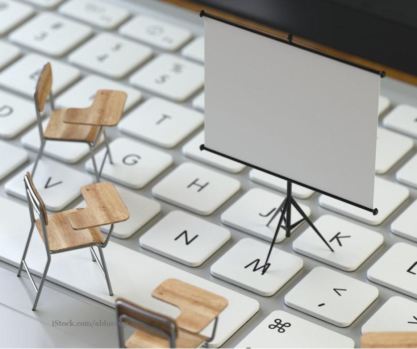 Zu sehen ist eine Tastatur und Miniatur Konferenzstühle und eine Leinwand.
