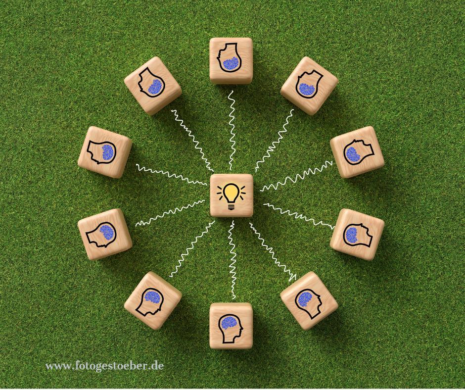 eine gruene Wise mit im Kreis angeordneten Holzkloetzen. Auf den Kloetzen sind Koepfe abgebildet. In der Mitte ein Klotz mit einer Abbildung Gluehbirne.