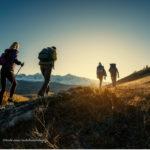 Vier Personen wandern einen Berg bei Sonnenaufgang hinauf.