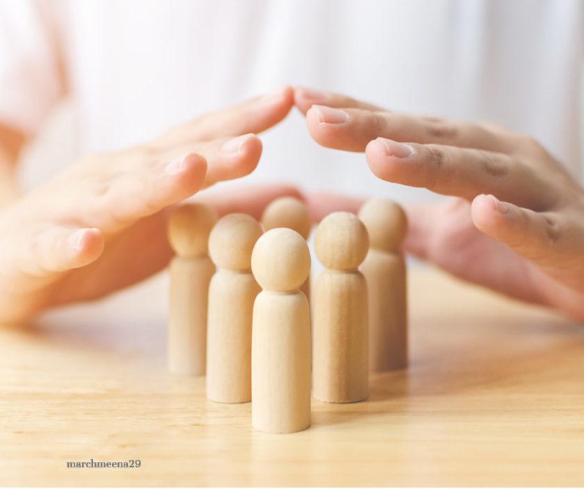 Zwei Hände werden schützend über eine Gruppe Holzfiguren gehalten