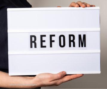 """Zu sehen ist der Text """"Reform"""" auf weißen Lichtbox."""