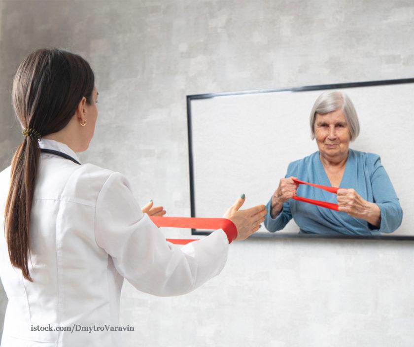 Physiotherapeutin zeigt älterer dame über Video eine Bewegungsübung